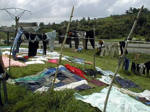 After being washed, the clothes are carried to a designated place for each washer where they are spread out on the grass to dry in the sun ... often very close to the expressway