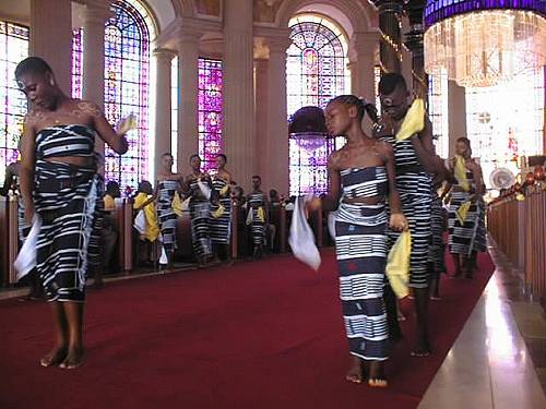 Ivorian girls using traditional dance steps to exit the Cathedral after carrying the offering to the altar.